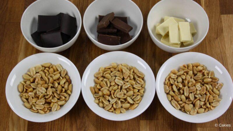 6 kommen op een houten ondergrond. 3 kommen met pinda's, 1 kom met stukjes pure chocolade, 1 kom met stukjes witte chocolade, 1 kom met stukjes melkchocolade
