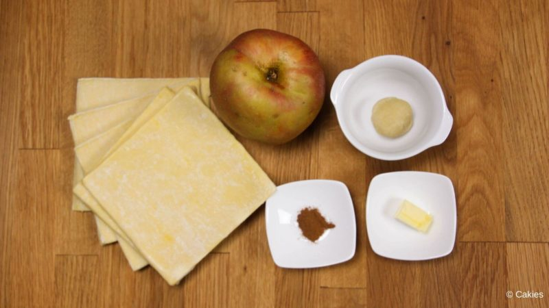 Ingredients for Dutch apple beignets with puff pastry on a wooden surface.